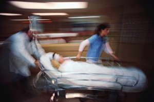 A trauma team physician and nurse push a patient into the operating room.